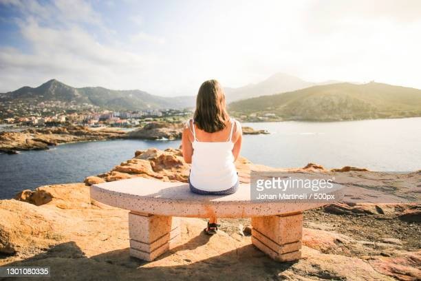woman sitting on bench looking at view over bay - martinelli stock pictures, royalty-free photos & images