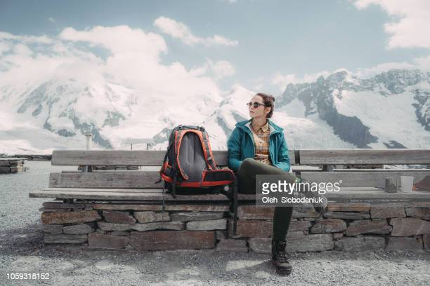 woman sitting on bench on the background of  the glacier in swiss alps - switzerland stock pictures, royalty-free photos & images