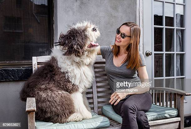 Woman sitting on bench outside with her pet dog