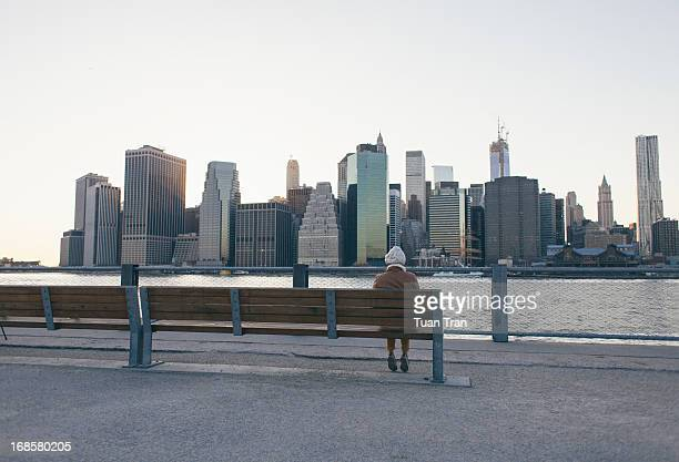 Woman sitting on bench overlooking Manhattan