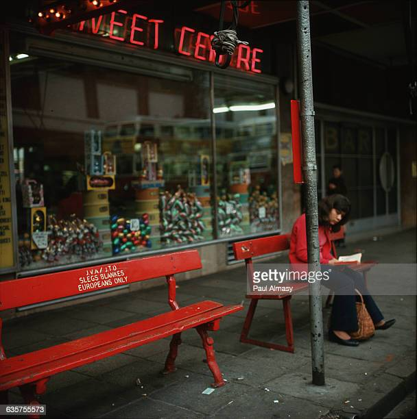 A woman sitting on bench reserved for the use of whites only outside a sweet shop in the city of Johannesburg in South Africa