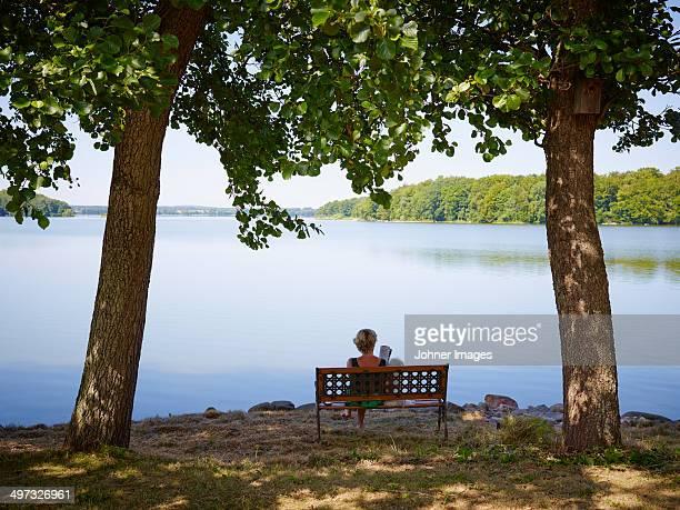 Woman sitting on bench, Skane, Sweden