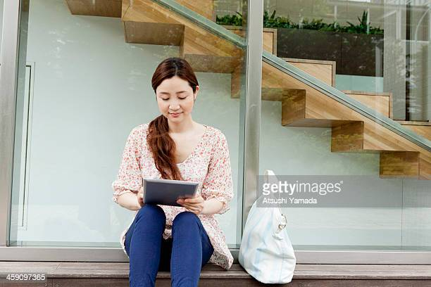 Woman sitting on bench,using digital tablet