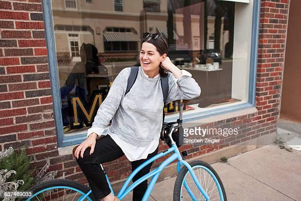 Woman sitting on bike laughing