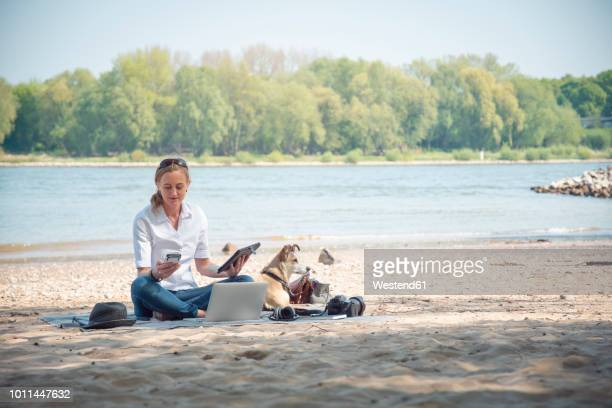 Woman sitting on blanket at a river with dog using portable devices
