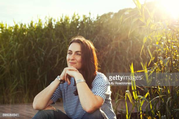 Woman sitting on boardwalk looking out at view