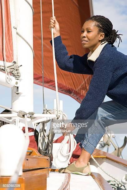 Femme assise sur un bateau tenant la corde