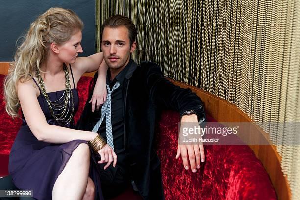 Woman sitting on boyfriend's lap in bar