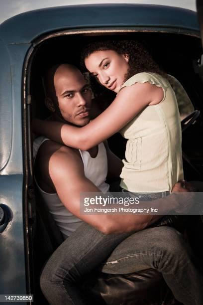 Woman sitting on boyfriend's lap in truck
