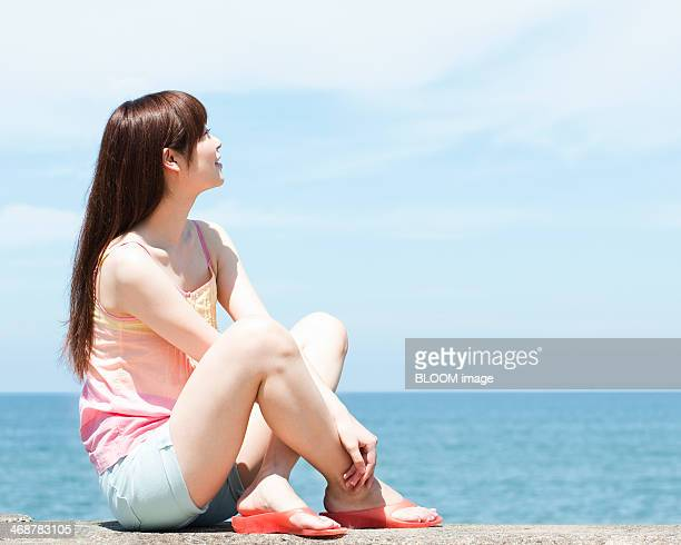 Woman Sitting On Breakwater