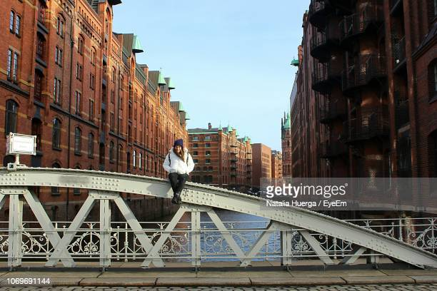 woman sitting on bridge over canal amidst buildings - hamburg germany stock pictures, royalty-free photos & images