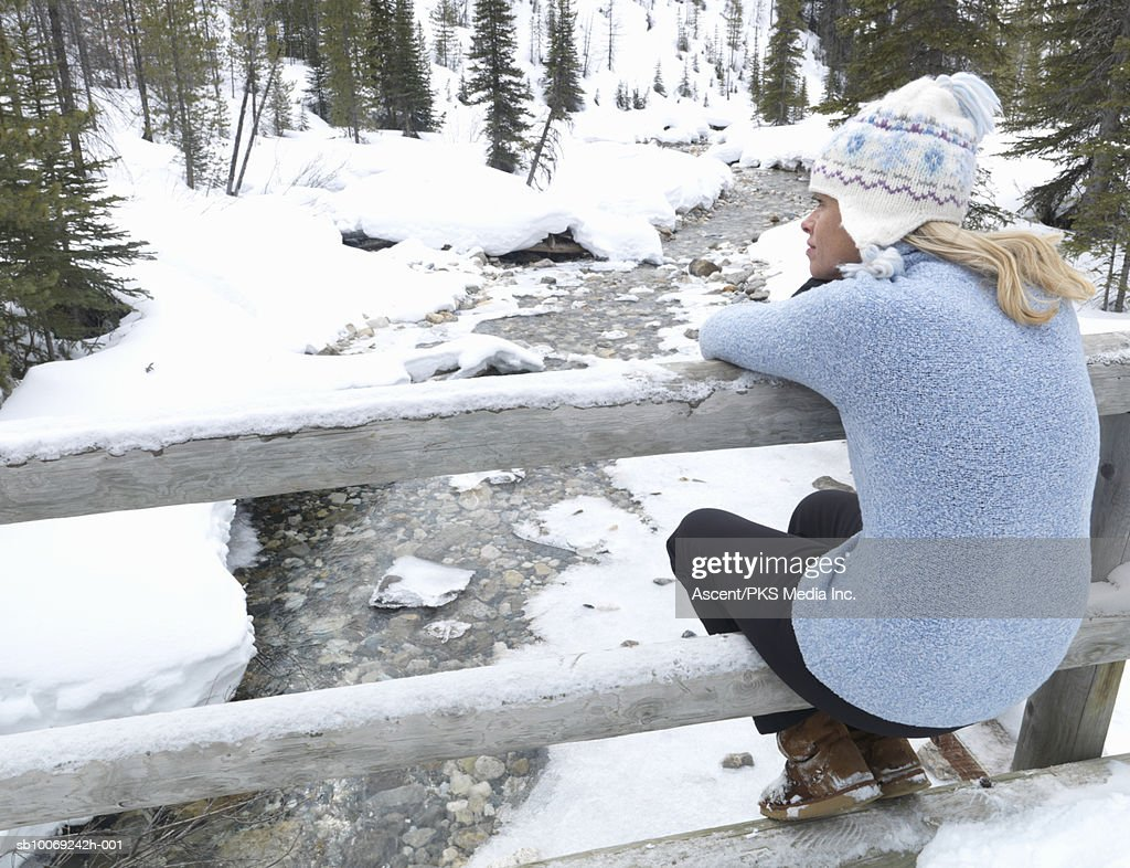 Woman Sitting on bridge rail, looking at snowcapped stream, rear view : Stockfoto