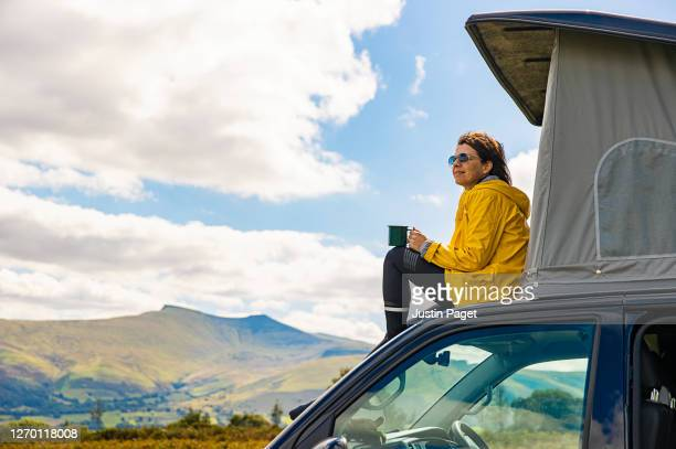 woman sitting on campervan in the brecon beacons - travel stock pictures, royalty-free photos & images