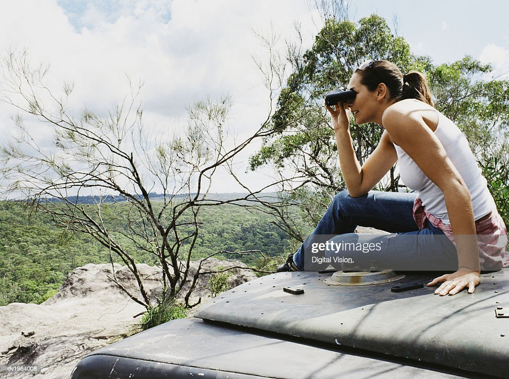 Woman Sitting on Car Bonnet Looking Through a Pair of Binoculars : Stock Photo