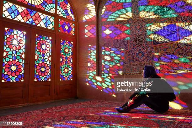 woman sitting on carpet against stained glass - shiraz stock pictures, royalty-free photos & images