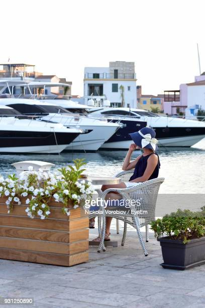 woman sitting on chair at harbor against boats on river - republic of cyprus stock pictures, royalty-free photos & images