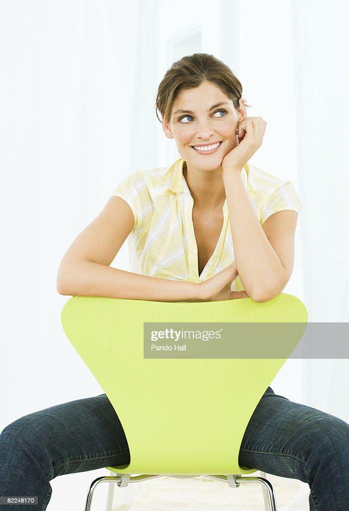 Woman sitting on chair, head on hand, smiling : Stock Photo