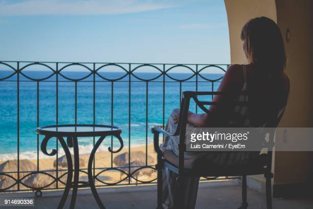 Woman Sitting On Chair In Balcony Against Sea And Sky