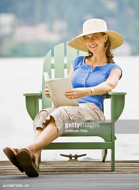 woman sitting on chair, reading book, smiling, portrait - legs crossed at ankle stock pictures, royalty-free photos & images