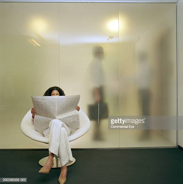 Woman sitting on chair, reading newspaper, two men behind glass wall