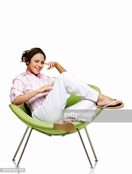 Woman sitting on chair, smiling, portrait