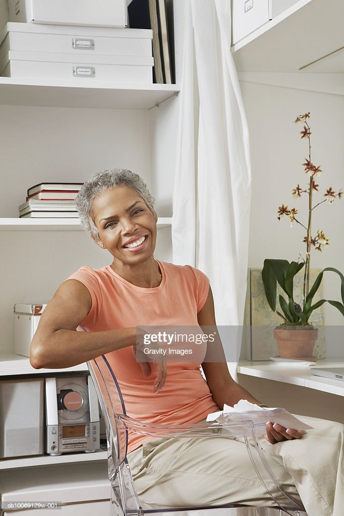 Woman sitting on chair with holding envelop, smiling, portrait : Stockfoto