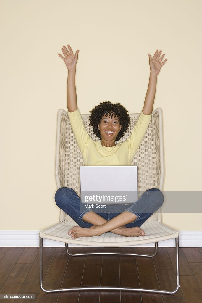Woman sitting on chair with laptop, raising arms, portrait : Stockfoto