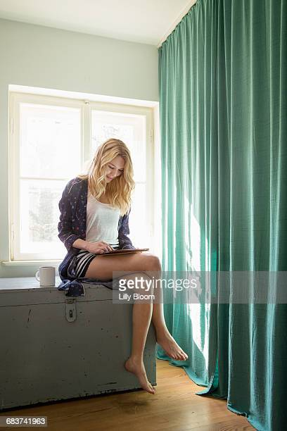 woman sitting on chest using digital tablet - world at your fingertips stock pictures, royalty-free photos & images
