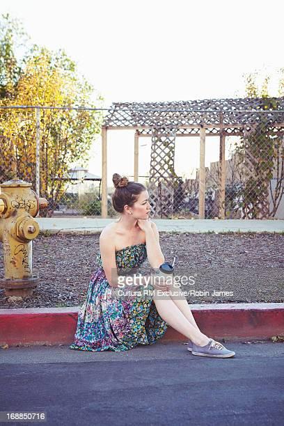 Woman sitting on city street curb