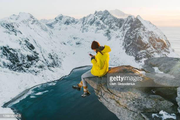 woman sitting on cliff and using smartphone on lofoten island in snow - top garment stock pictures, royalty-free photos & images