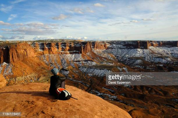 woman sitting on cliff at green river overlook in canyonlands national park in winter - canyonlands national park stock pictures, royalty-free photos & images