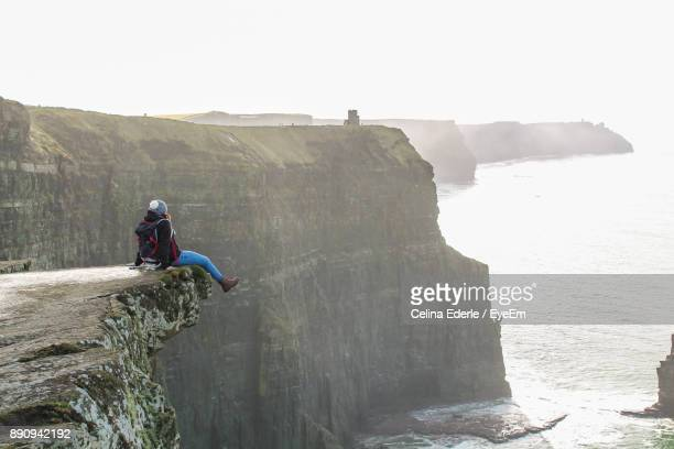 Woman Sitting On Cliff Over Sea