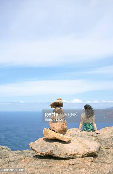 Woman sitting on cliff top beside pile of rocks, looking towards sea
