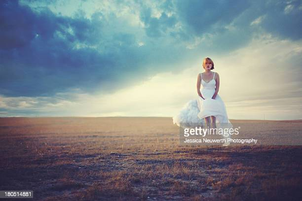 Woman sitting on cloud floating over field