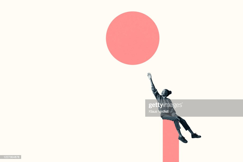 Woman sitting on column while reaching for circle : Stockfoto