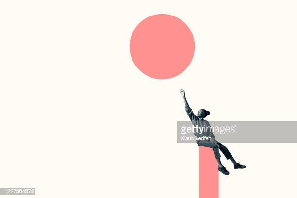 woman sitting on column while reaching for circle - lebensziel stock-fotos und bilder