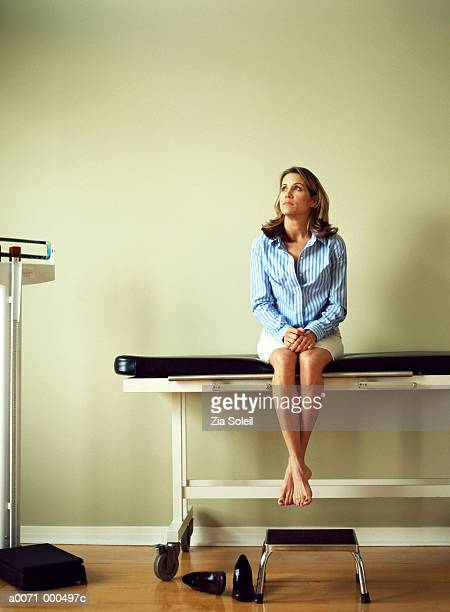 woman sitting on couch in doctor's surgery - examination table stock pictures, royalty-free photos & images