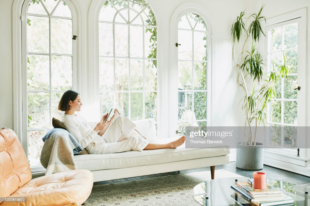 Woman sitting on couch in living room reading on digital tablet : Stock Photo