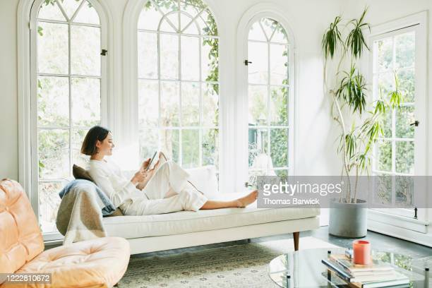 woman sitting on couch in living room reading on digital tablet - despreocupado imagens e fotografias de stock