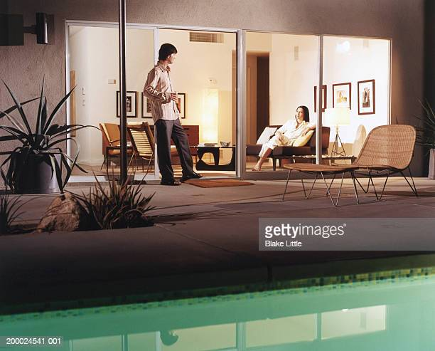 Woman sitting on couch looking through glass door at man on patio
