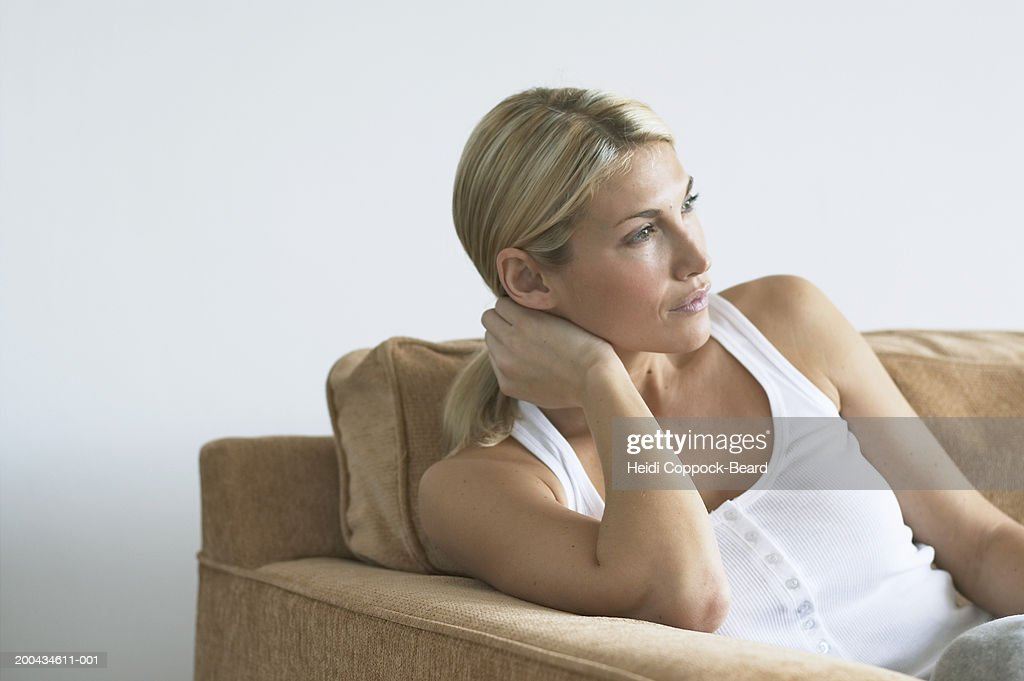 Woman sitting on couch, side view, close-up : Stock Photo