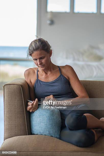 Woman Sitting on Couch Text Messaging