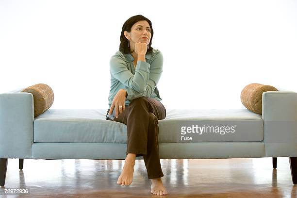 woman sitting on couch thinking - hand on chin stock pictures, royalty-free photos & images
