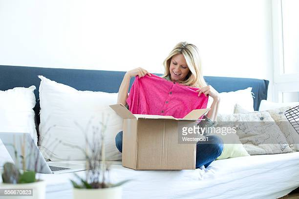 Woman sitting on couch unpacking online shopping purchase