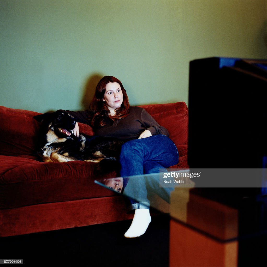 Woman sitting on couch with dog, watching television : Stock Photo