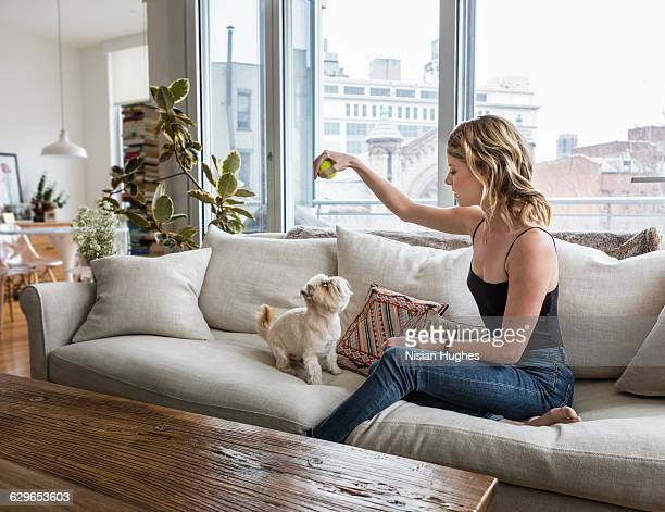 Woman sitting on couch with her pet dog