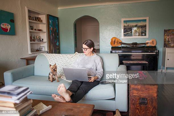 woman sitting on couch with laptop computer - canapé photos et images de collection