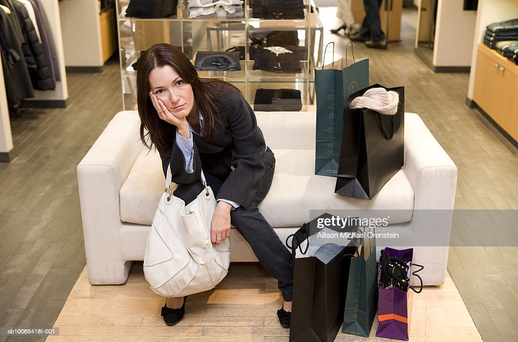Woman sitting on couch with shopping bags : Foto stock