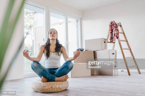 Woman sitting on cushion in her new apartment, meditating
