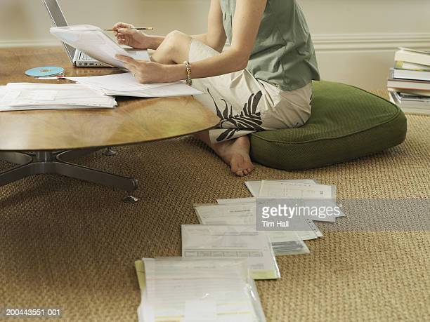 Woman sitting on cushion with documents using laptop, low section
